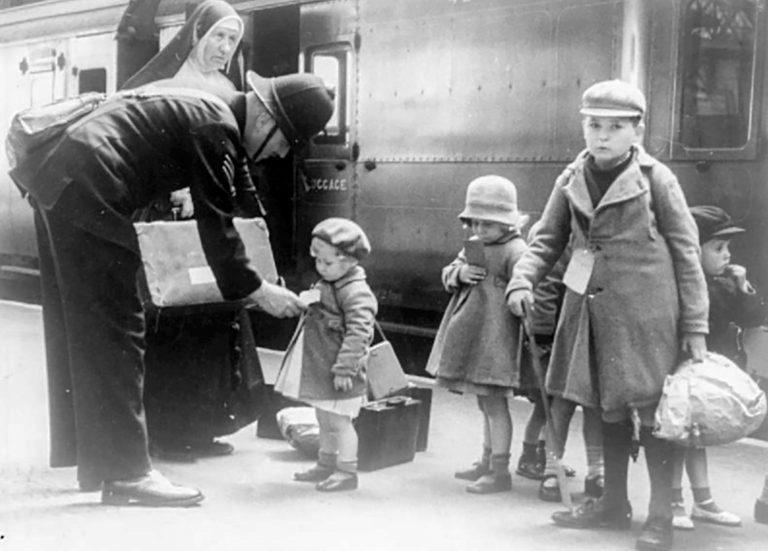"""Ankunft eines """"Kindertransportes"""" auf einem Londoner Bahnhof, Dezember 1938 Mitte November 1938 gestattet die britische Regierung die Aufnahme von jüdischen Kindern und Jugendlichen in Großbritannien, nachdem sich jüdische Organisationen zur Übernahme der Reisekosten und zur Suche von Pflegefamilien verpflichtet haben. Zwischen Dezember 1938 und September 1939 kommen 10.000 junge Menschen ins Land. Da Pflegefamilien fehlen, werden viele als Dienstpersonal ausgenutzt oder in Heimen untergebracht. Die Trennung von den Eltern und die Ermordung ihrer Angehörigen im Holocaust hinterlassen bei vielen der geretteten Kinder schwere Traumata. Imperial War Museum, London, LN 6194"""