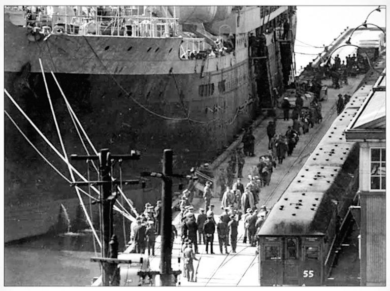 """Ankunft der HMT (His Majesty's Transport) Dunera in Sydney am 6. September 1940 An Bord befinden sich fast 2.000 jüdische und politische Flüchtlinge, Hunderte weitere Personen – darunter deutsche Kriegsgefangene – haben das Schiff bereits in Melbourne verlassen. Die Männer gehören zu den mehr als 8.000 Internierten, die Großbritannien als """"Enemy Aliens"""" nach Australien und Kanada abschiebt. An Bord herrschen katastrophale Bedingungen. The Sydney Morning Herald, 7. September 1940 / Pyrmont History Group, Sydney"""