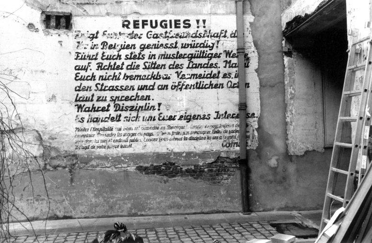 Mauerinschrift in einem Innenhof in der Brüsseler Rue Roger van der Weyden 25 aus den 1930er-Jahren Vor Beginn des Krieges mahnt eine deutsche Mauerinschrift in einem Brüsseler Innenhof Geflüchtete, die belgische Gastfreundschaft zu achten. Flüchtlinge kommen meist mittellos in die großen Städte, ihre Zahl steigt nach dem Novemberpogrom auf monatlich 2.000. Finanzielle Unterstützung erfahren sie durch Hilfsorganisationen und Privatpersonen; erst ab Mitte 1939 beteiligt sich der belgische Staat hieran. Foto: Christian Carez Brüssel / Collection Cegesoma, Brüssel, DO4 AGR 36390