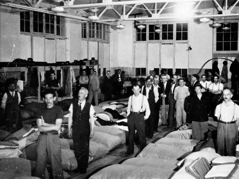 Jüdische Flüchtlinge im Aufnahmelager Diepoldsau, Sankt Gallen, 20.8.1938 Für die Unterbringung, den Lebensunterhalt und die Kosten der Weiterwanderung müssen die schweizerischen jüdischen Organisationen aufkommen, die auch das Flüchtlingslager Diepoldsau betreiben. Da Juden aber nie mehr als 0,5 Prozent der Schweizer Bevölkerung ausmachen, sind sie damit hoffnungslos überfordert, so dass ab 1939 dasAmerican Jewish Joint Distribution Committeemehr als die Hälfte der Kosten für die Unterstützung der jüdischen Flüchtlinge in der Schweiz trägt. The New York Times, Paris Office / National Archives, College Park, MD