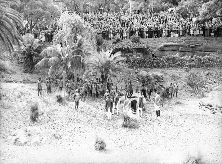 """Schaulustige beobachten die Nachstellung der Landung der """"First Fleet"""" in Farm Cove, 26. Januar 1938 In den Feiern zum 150. Jahrestag der Ankunft der ersten britischen Sträflinge im heutigen Sydney kommt das Selbstverständnis der Mehrheitsbevölkerung als """"White Australia"""" zum Ausdruck. Bis heute ist der 26. Januar als """"Australia Day"""" Nationalfeiertag. State Library of New South Wales, Sydney"""