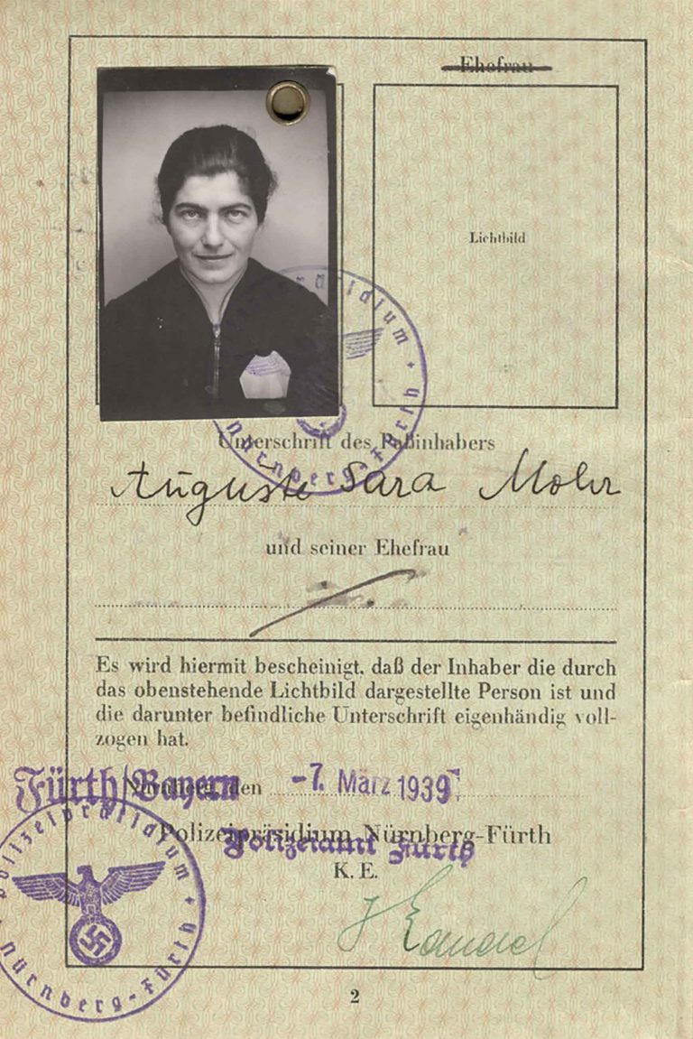 "Nürnberg-Fürth police headquarters: passport for Auguste Mohr, March 7, 1939 Auguste Mohr's passport, which already bears the compulsory Jewish name ""Sara"" and is stamped with the letter ""J,"" holds an entry visa from the Haitian consulate in Hamburg, dated March 9, 1939, and is valid for one year. With the confirmation of this visa, Auguste Mohr attains the release of her husband Ernst, who has been imprisoned in the Dachau concentration camp since the November pogrom in 1938, and is able to immigrate to Haiti with him and their two small children. Private collection Harriet und Bill Mohr, Menlo Park, CA"