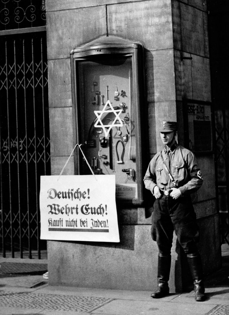 """SA member next to a poster with the inscription """"Germans! Fight back! Don't buy from Jews!"""" on April 1, 1933 in front of the Tietz department store in Berlin The morning of April 1, 1933 sees the start of a nationwide boycott of Jewish businesses, doctors, lawyers and notaries organized by theCentral Committee to Repulse Jewish Atrocity and Boycott Agitationunder Julius Streicher, Gauleiter of the Bavarian region of Franconia. The police and the judiciary do nothing to curb these anti-Jewish actions. The New York Times, Paris Office / National Archives, College Park, MD"""