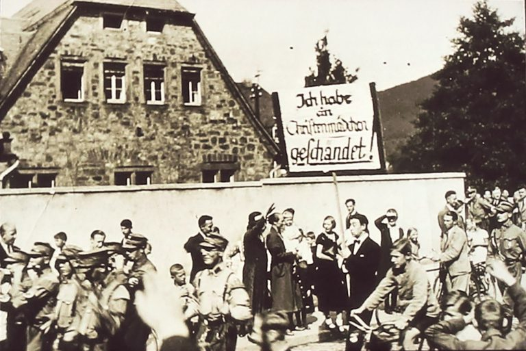 """The SA parades a Jewish student through the city of Marburg with a sign saying, """"I have defiled a Christian girl!"""" August 24, 1933 Even before the """"Nuremberg Laws"""" are enacted, numerous places see attacks against Jews for alleged """"racial defilement."""" A rash of pogroms in smaller towns prompts many Jews to choose the anonymity of bigger cities, where they are less exposed to this form of persecution. Archiv der Stabsstelle Presse- und Öffentlichkeitsarbeit der Stadt Marburg"""