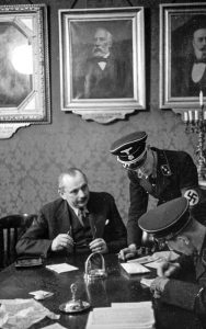 Raid at theJewish Community Vienna, March 18, 1938 The photo shows (l. to r.) Josef Löwenherz, director of the Jewish Community Vienna (IKG), and SD leaders Herbert Hagen and Adolf Eichmann. Receipts for campaign donations to the pro-independence Fatherland Front that are found during the raid serve as a pretext for imposing reparations of 500,000 Reichsmarks on the Jews of Vienna, which are to paid through a fifty percent surcharge on the tax on religious organizations. Bundesarchiv-Bildarchiv, Koblenz, Bild 152-65-15A