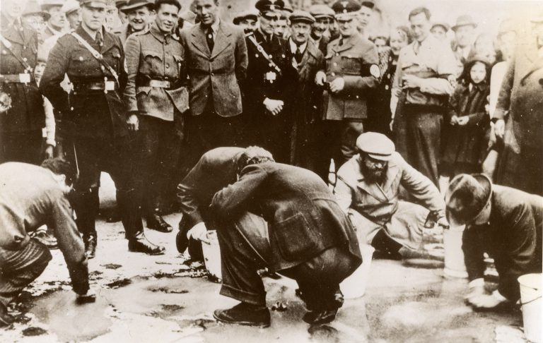 """Uniformed Nazis and civilians observe a """"Reibpartie"""" (""""scrub group"""") in Vienna, March 1938 In Vienna, Jews are forced to use corrosive lye to remove slogans of the Fatherland Front from the streets. The Fatherland Front had campaigned for people to vote yes in the referendum on Austrian independence that was scheduled by Chancellor Kurt Schuschnigg. Under pressure from Hitler, the referendum is cancelled. Jewish businesses are defaced, plundered, and seized through """"wild Aryanization."""" American Jewish Joint Distribution Committee Archives, New York, NY"""