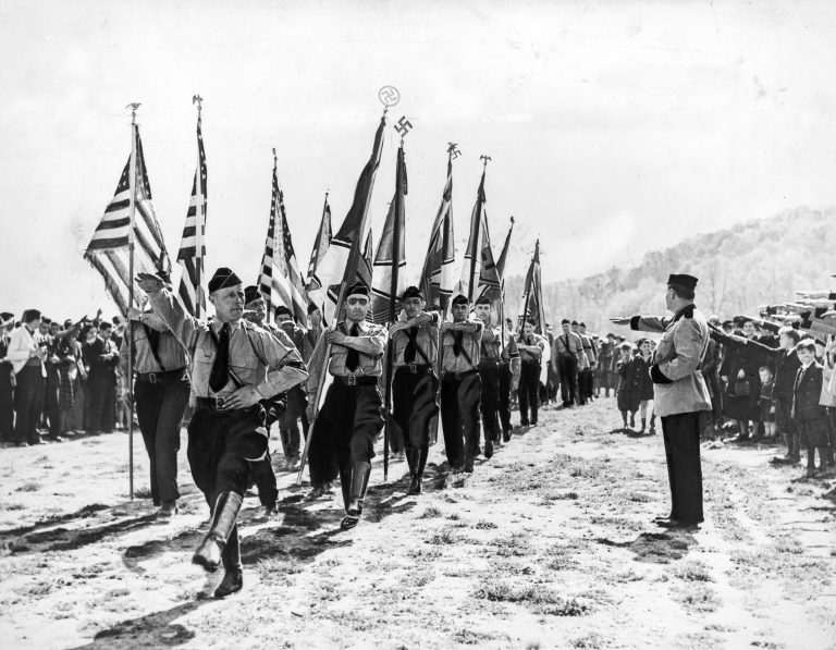 "Inspection of a May Day parade at ""Camp Nordland"" in Andover, NJ, by Fritz Kuhn, the leader of the German-American Bund, May 1, 1938  The German-American Bund is established in 1936 as an organization of about 25,000 Americans of German ancestry. Its leader, Fritz Kuhn, who became a naturalized US citizen in 1934, declares the Jews to be the enemies of America and dubs President Roosevelt's New Deal the ""Jew Deal."" He quickly becomes the most famous antisemite in America. The Bund's 8,000 ""Storm Troopers"" perpetrate brutal acts against Jews. Bettmann Archive / Getty Images"